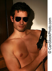 Young man with gun - A young man with a gun and sunglasses ...
