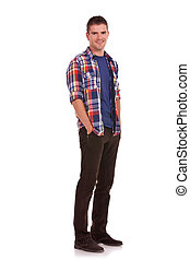 Full length picture of a casual young man standing with his hands tucked in his pockets, on white background