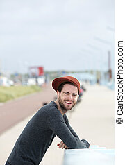 Young man with hat posing outdoors