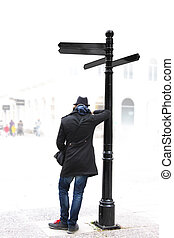 Young man with hat standing by signpost