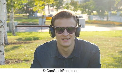Young man with headphones at green grass