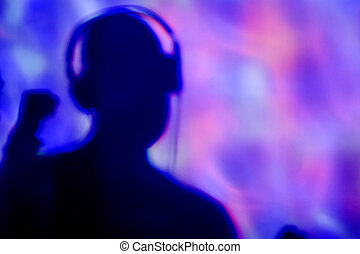 young man with headphones in a dance club - the silhouette ...