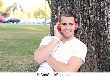 Young man with headphones in a park.