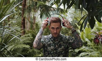 Young man with headphones standing in botanical garden.