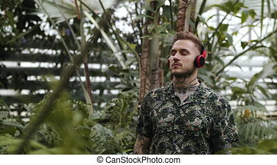 Young man with headphones standing in botanical garden, ...