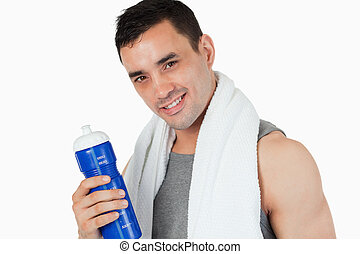 Young man with his bottle after training