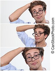 young man with his glasses askew and hand to his head