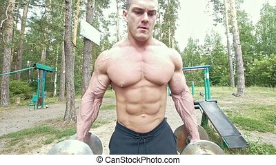 Young man with his huge muscular arms veins picks up heavy dumbbells in forest