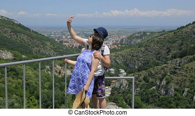 Young man with his wife making selfie on mountain