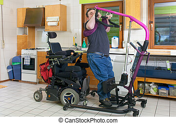Young man with infantile cerebral palsy from birth complications using a patient lift to move from his bed to a multifunctional wheelchair