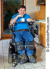 Spastic young man with infantile cerebral palsy caused by complications at birth sitting in a multifunctional wheelchair enjoying a mug of beverage drinking through a straw
