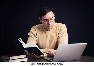 man with laptop and book