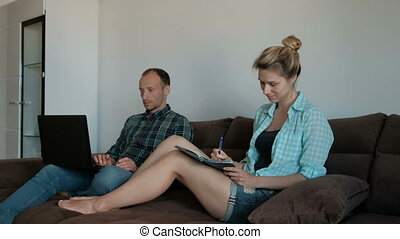 Young man with laptop and woman writing sitting on couch indoors.