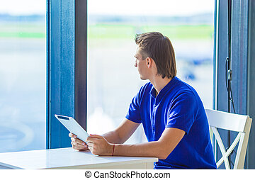 Young man with laptop at airport cafe while waiting for boarding