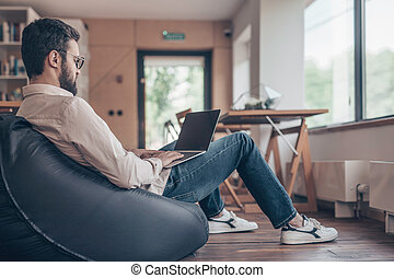 Young man with laptop at work