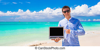 Young man with laptop during beach vacation