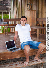 Young man with laptop on exotic resort outdoor