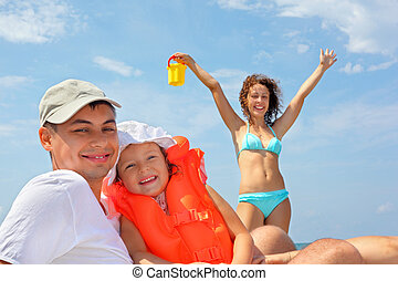 young man with little girl in orange lifejacket and beautiful woman with plastic toy bucket, woman lifted hands upwards