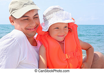 young man with little girl in orange lifejacket on beach