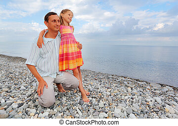 young man with little girl on stony beach