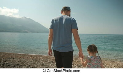 Young man with little girl walking along seashore on sunny day outdoors.