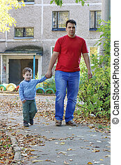 Young man with little son go on asphalt path near building at fall