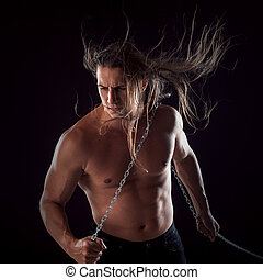 Young man with long hair dragging something behind him....