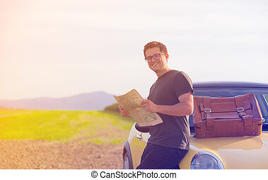 Young man with map standing near a car