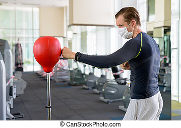 Young man with mask for protection from corona virus outbreak boxing at gym during corona virus covid-19