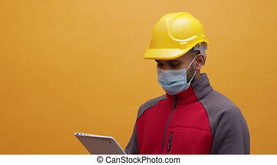 Young man with medical mask and yellow hard hat using tablet and inspecting construction site. High quality 4k footage