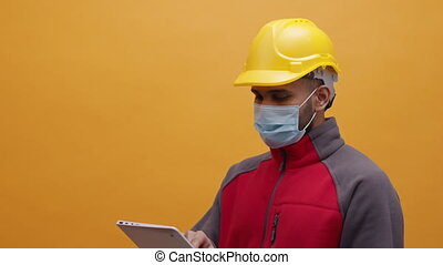 Young man with medical mask and yellow hard hat using tablet. High quality 4k footage