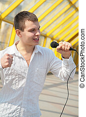 young man with microphone on footbridge