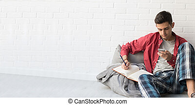 young man with mobile phone and agenda at home