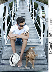 young man with mobile phone and dog on the pier