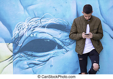 young man with mobile phone on street