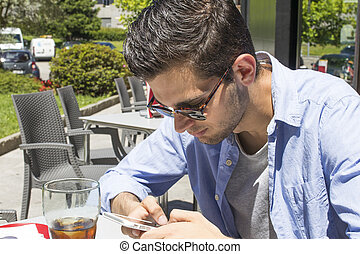young man with mobile phone on the terrace of the cafeteria
