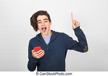 young man with mobile phone on white wall background