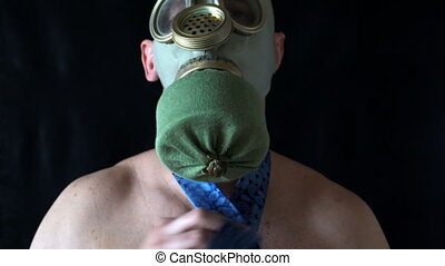 young man with naked torso in the mask straightens his tie....