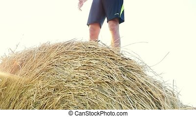 Young man with naked torso raises his hands in a field in slowmotion standing on the haystack during a beautiful sunset