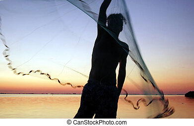 young man with net - young man throwing castnet at sunset on...