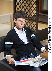 Young man with newspaper across table.