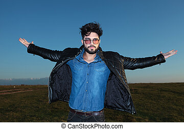 young man with open arms against blue sky