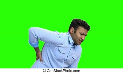 Young man with pain in kidneys on green screen. Handsome...