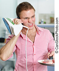 Young man with pan and iron speaking on the phone on kitchen background