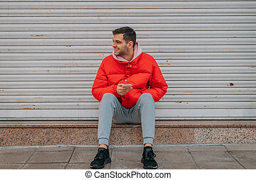 young man with phone sitting on city street
