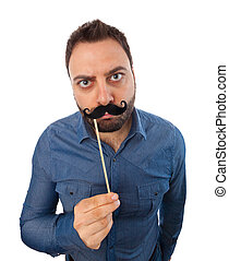 Young man with photo booth mustache on white background