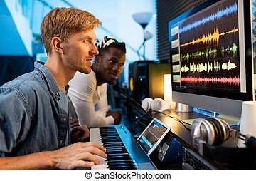 Young man with pianoboard looking at computer screen during ...