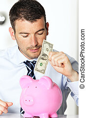 young man with pink piggy bank and bill