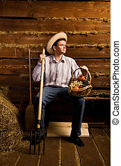 young man with pitchfork,with basket of fruit and in straw hat sitting on bench in wooden log hut