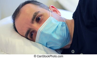 Young man with protective mask and covid 19 symptoms staying in isolation at home. 4k